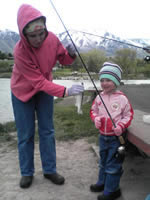 [Photo: Inez and Esperanza at Salem Pond, Holding a fish]